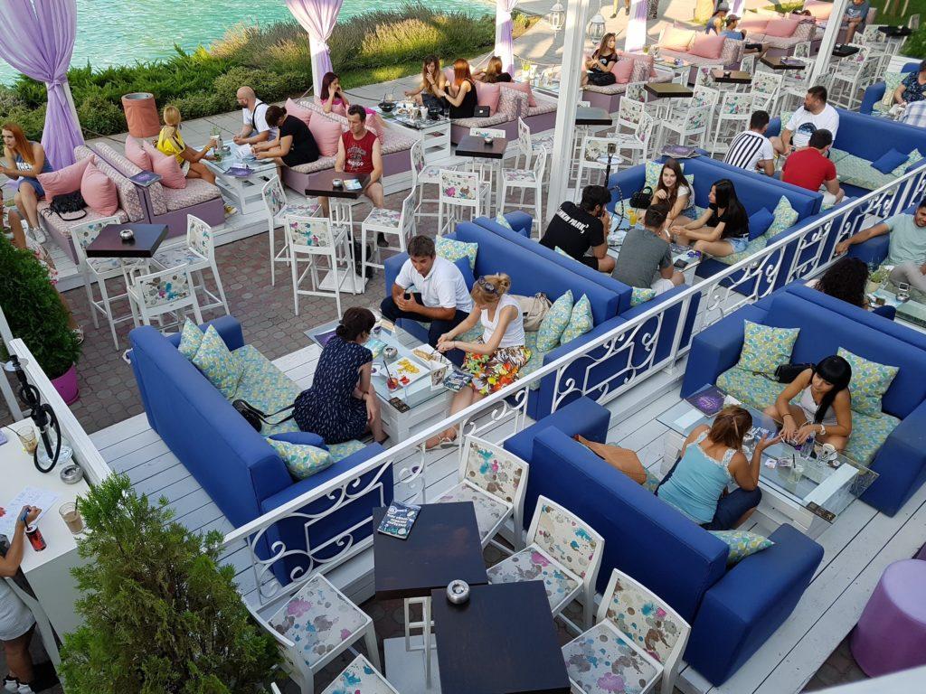 Uitzicht op loungebanken met mensen erop, vanaf de eerste verdieping van de Morado bar.
