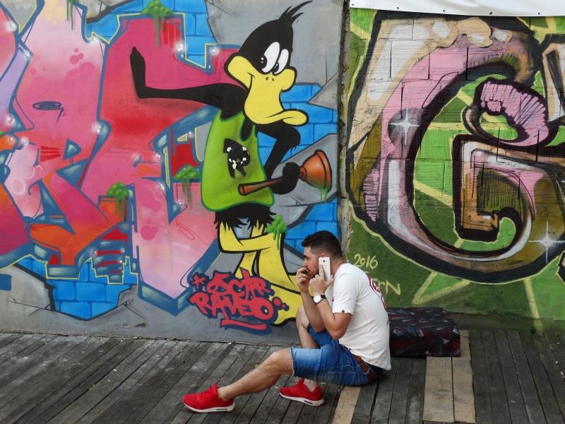 Loony tunes figuur streetart met daaronder bellende man.