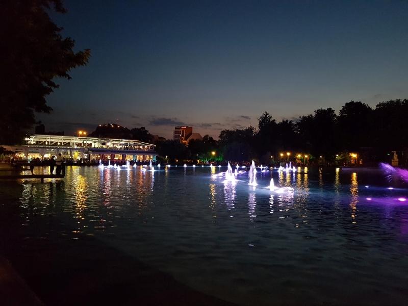 Verlichte fonteinen in het donker met op de achtergrond de Morado bar.