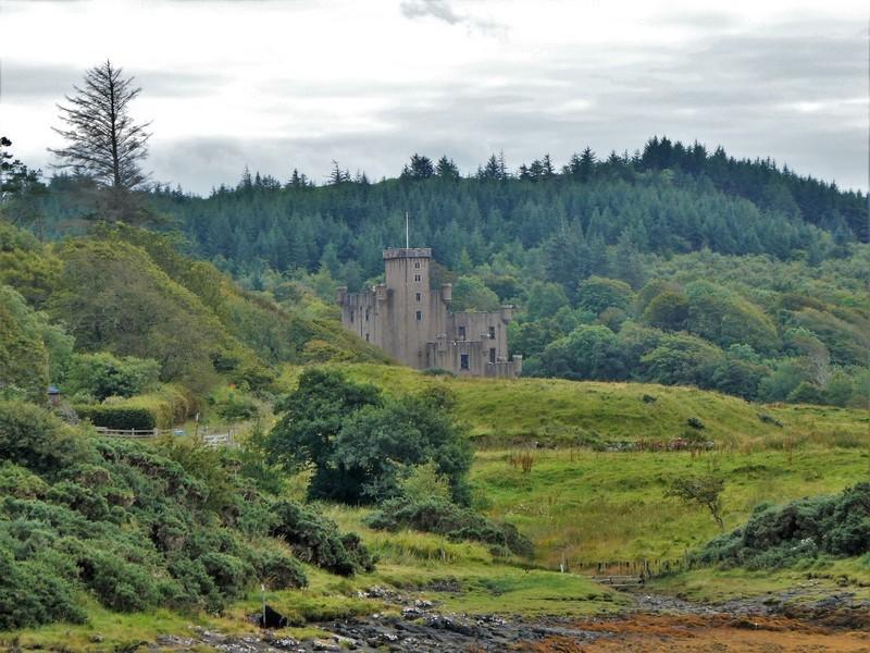 Kasteel Dunvegan omringd door groene bomen en struiken. Isle of Skye