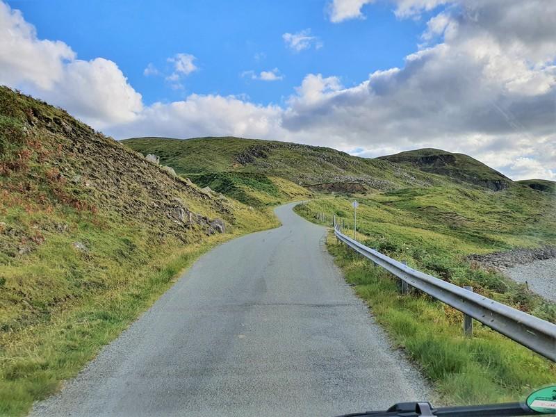 Smalle weg langs de kust, van het eiland Skye, door groene heuvels