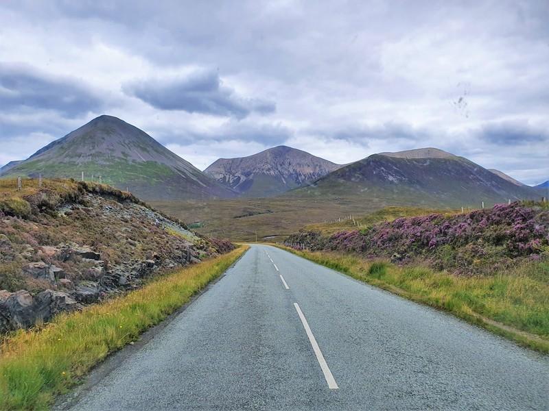 Rondrit over het eiland Skye. Weg met bloeiende hei aan weerszijden en heuvels in de verte.