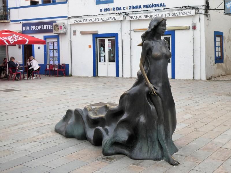 Het beeld van Floripes, vrouw met lange, golvende jurk en ontbloot been.