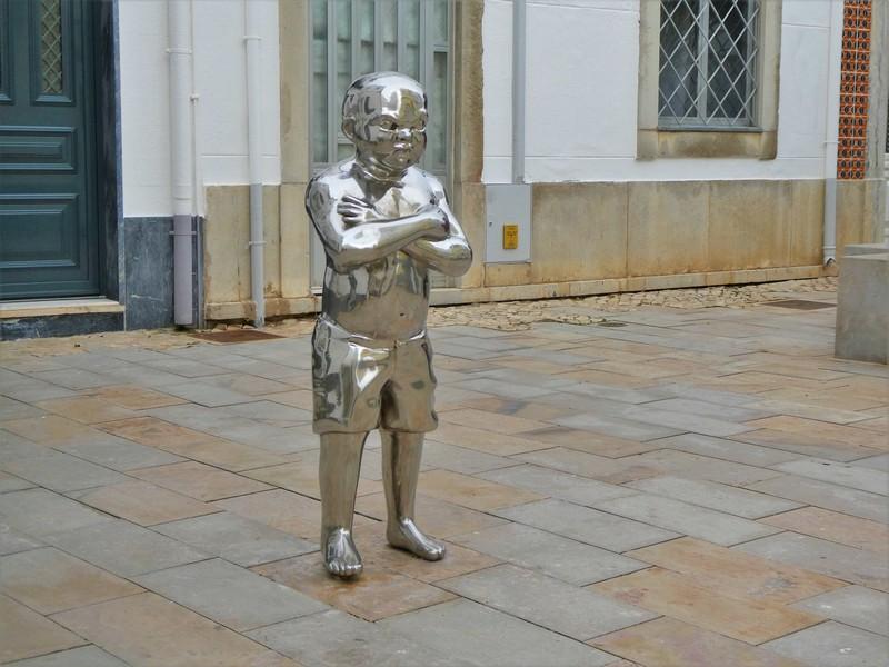 Glimmend metalen kunstwerk van dik jongetje met grote ogen en armen over elkaar.