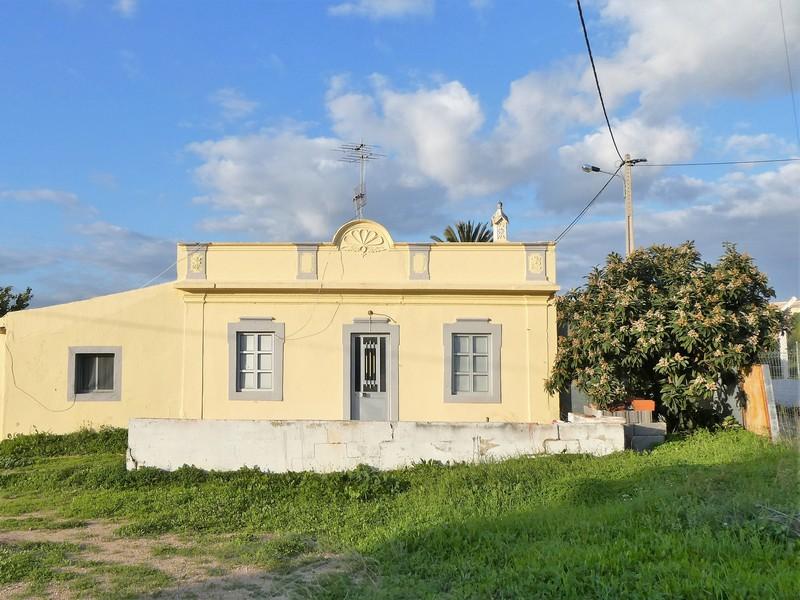 Geel huis met bloeiende boom ernaast, met gras ervoor en blauwe lucht erboven.