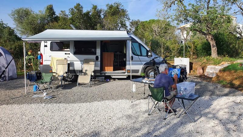 Onze camper en Wim die zit te schilderen