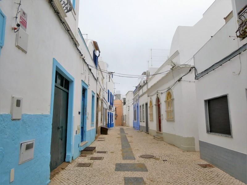 Steegje in de oude stad van Olhão. Witte huizen met gekleurde accenten.