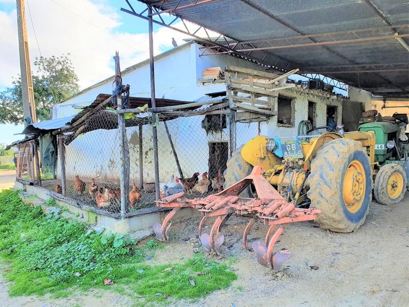 Landbouwvoertuigen met daarnaast kippen in een ren