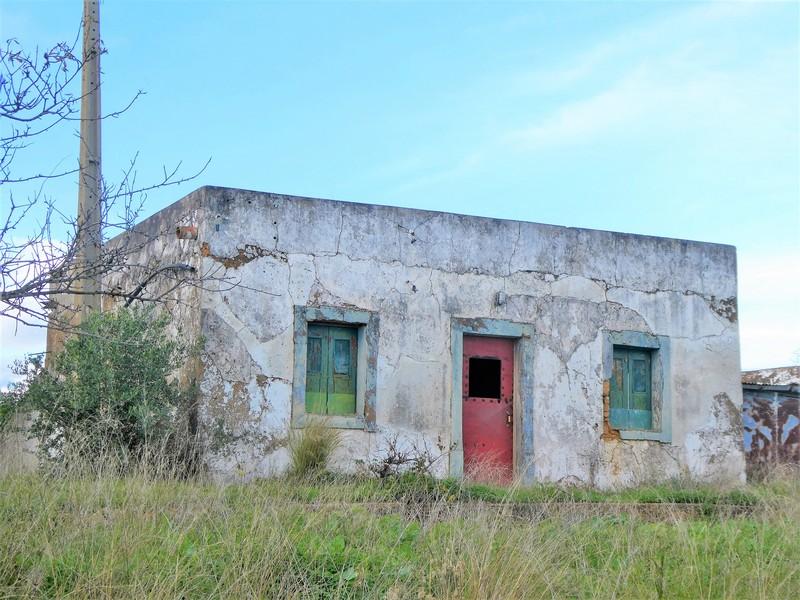 Vervallen gebouwtje met kleurrijke luiken en deur