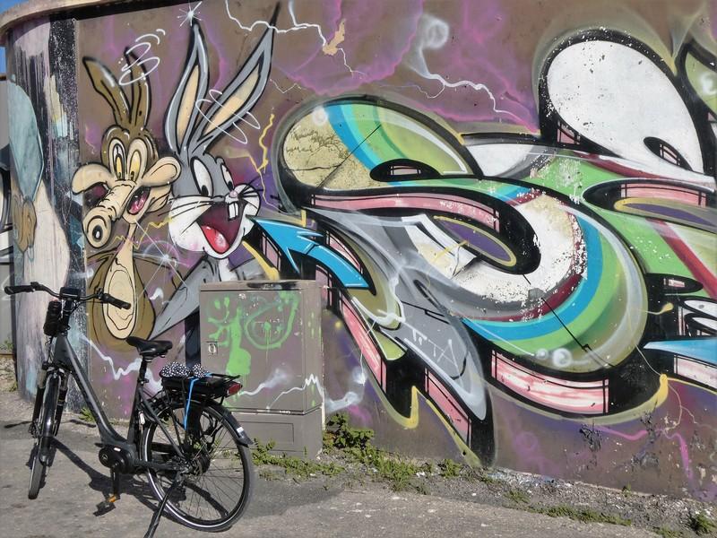 Mijn fiets voor een muurschildering met 2 loone tunes figuren met daarnaast een kleurrijke graffiti tag.