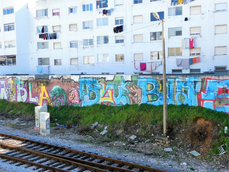 Graffiti - letters op de schutting langs de spoorlijn door Olhão, met daarachter wit flatgebouw met wasgoed.
