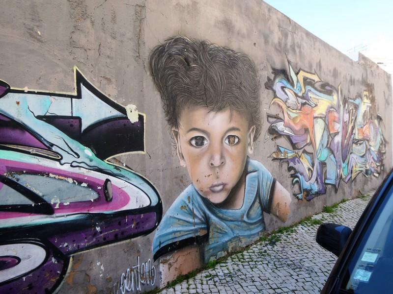 Streetart in Olhão - Mural van kleine jongen die indringend kijkt, met aan weerszijden graffiti.