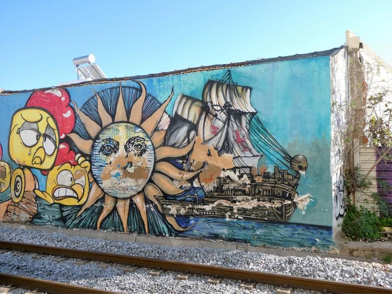 Muurschildering op blinde muur van gebouw langs het spoort, met stripachtige koppen van kippen, een zon en daarachter een oud zeilschip.