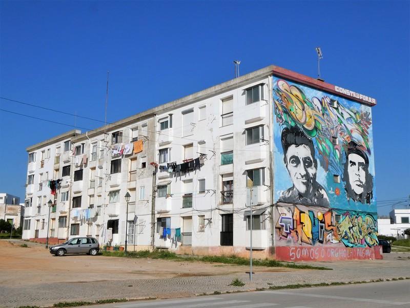 Flatgebouw met op de blinde muur 2 portretten in zwart wit plus graffiti