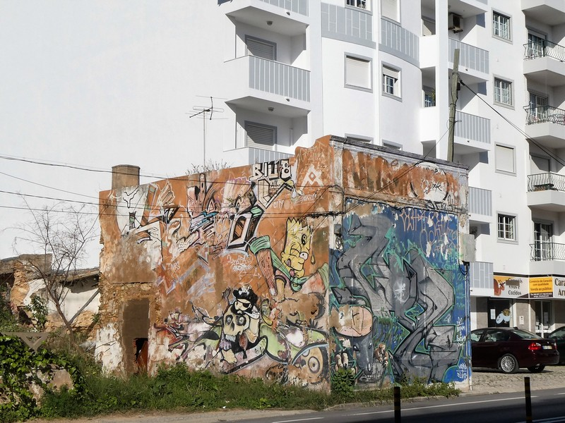 Oude en nieuwe graffiti en streetart op een vervallen gebouwtje langs de N125 door Olhão.