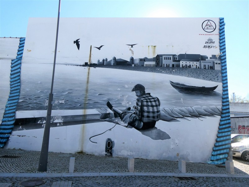 Afbeelding van visser die zittend op de kade zijn netten boet - mural op de Largo da Fábrica Velha