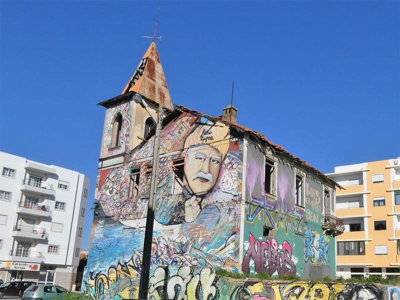 Vervallen gebouw  aan de doorgaande weg van Olhão met prachtige muurschilderingen - streetart