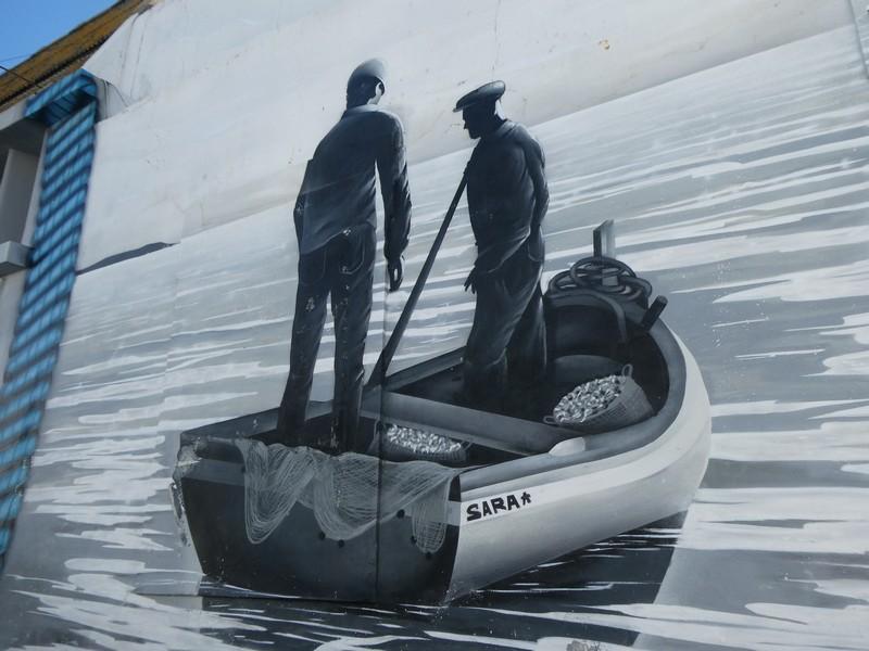 Afbeelding van twee mannen die in hun vissersbootje met de naam Sarah staan - mural op de Largo da Fábrica Velha