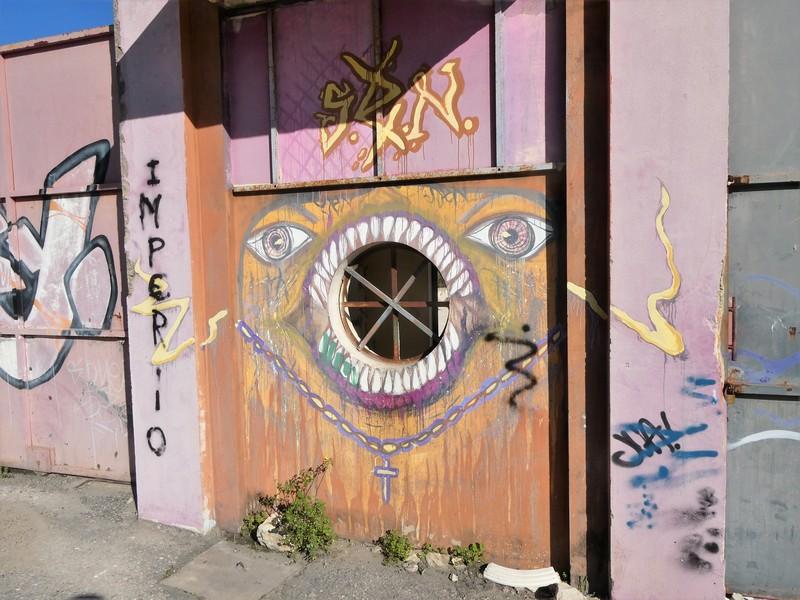 Mural met ogen, wijdopen mond rond een bestaand gat met spijlen, en ketting met kruisjes. Eromheen wat graffiti tags