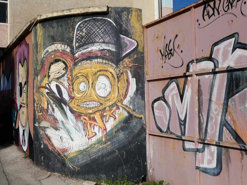 Muurschildering / mural met hoofd met heel wijdopen ogen en een mond vol met tanden. Streetart in Olhão