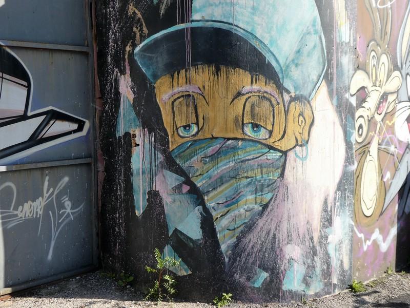 Muurschildering van jongetje met grote pet op zijn hoofd, doekje om zijn mond en ogen die bijna dichtzitten. Onderdeel van muur met streetart
