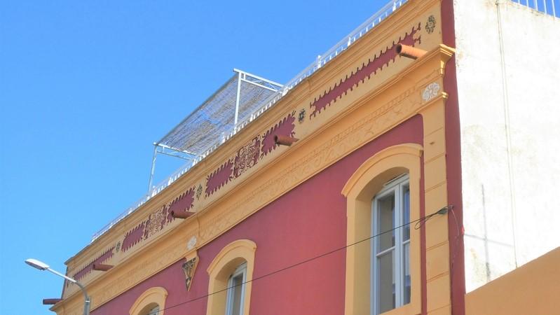 Daklijst van opgeknapt, rood/geel geschilderd) huis in het centrum van Moncarapacho