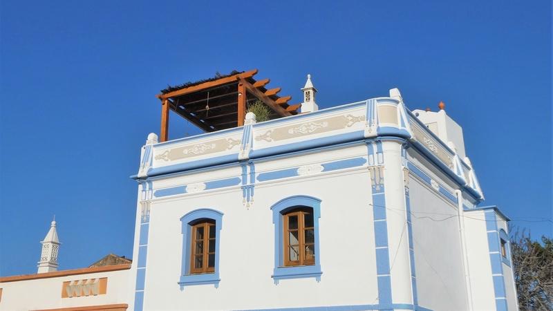 Daklijst van opgeknapt huis in het centrum van Moncarapacho. Ook twee schoorstenen die typisch zijn voor deze streek.