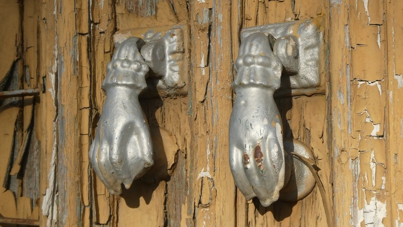 Deurkloppers in de vorm van handjes op afgebladderde deur.