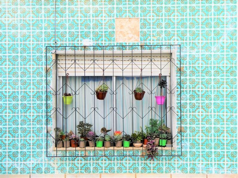 Huis waarvan de hele muur bekleed is met groene azulejos, oftewel tegels.