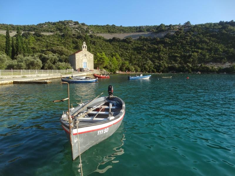 baai van Slano met vissersbootje op de voorgrond en kerkje op de achtergrond