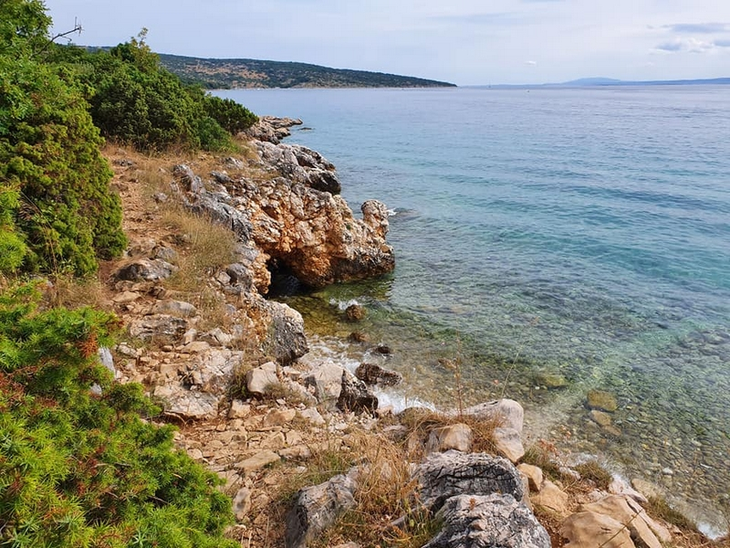 Rotsig kustpaadje bij Punat op Krk, met aan de ene kant struiken en bomen en aan de andere kant uitzicht op zee