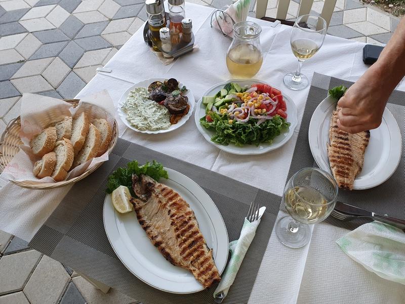 Gedekte tafel met salades, brood en gegrilde vis.