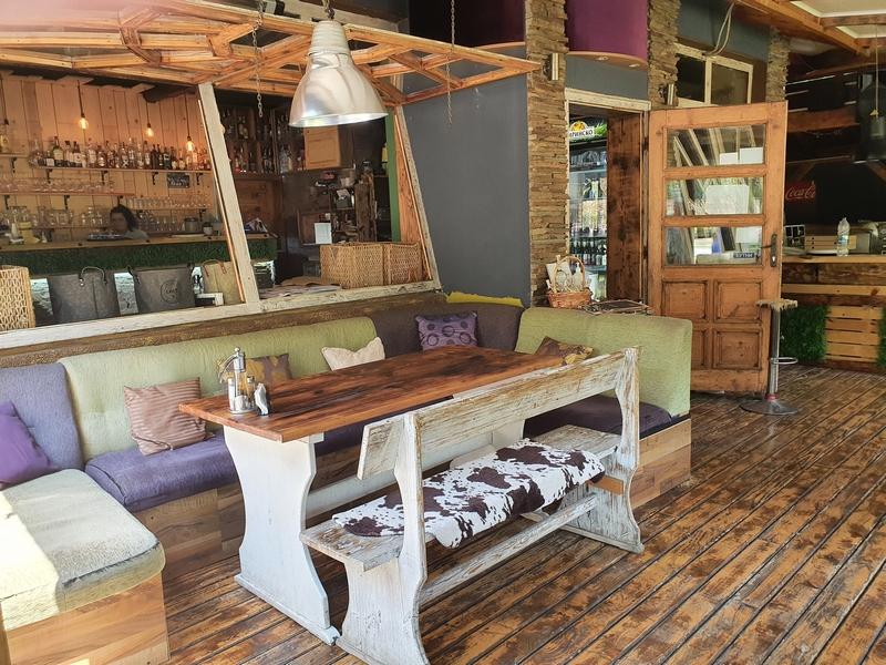 Interieur restaurant geyser met lange hoekbank met gekleurde kussens en houten tafel en bank met koeienvacht over de zitting.