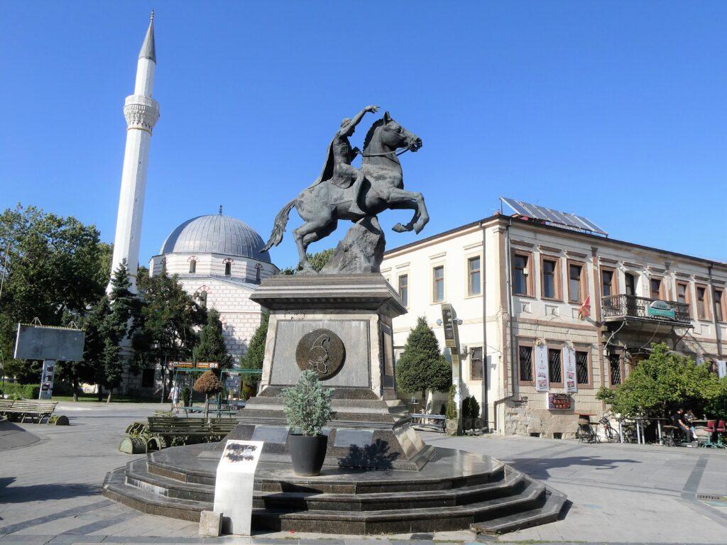 Standbeeld van Philippus II op zijn steigerende paard, met erachter een moskee met hoge minaret.