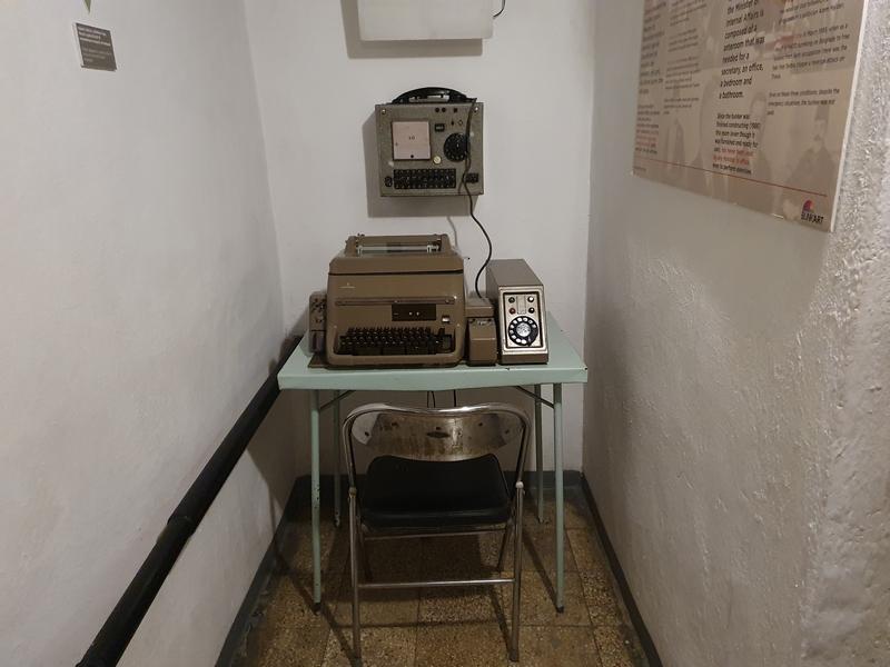 Kleine ruimte met afluisterappratuur aan de want en op tafeltje met typemachine erop en klapstoeltje ervoor.