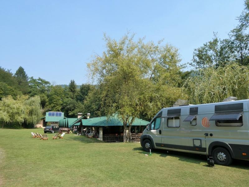 Op de voorgrond kampeerbus, daarachter het campingrestaurant.