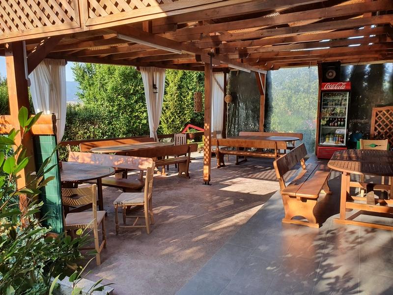 Terras met houten picknicktafels en -banken en houten overkapping