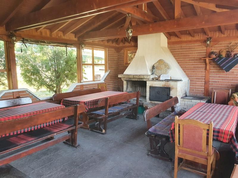 Binnenruimte met houten balkenplafond, open haard en stevige houten tafels met geruite tafelkleden en houten banken.
