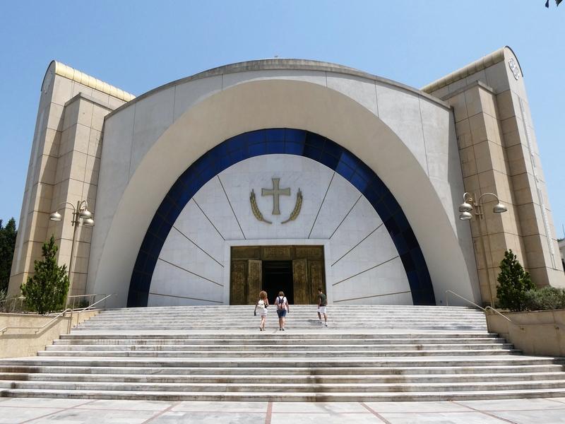Het grote, moderne gebouw van de kathedraal Shën Pali met een brede, niet steile trap ervoor.