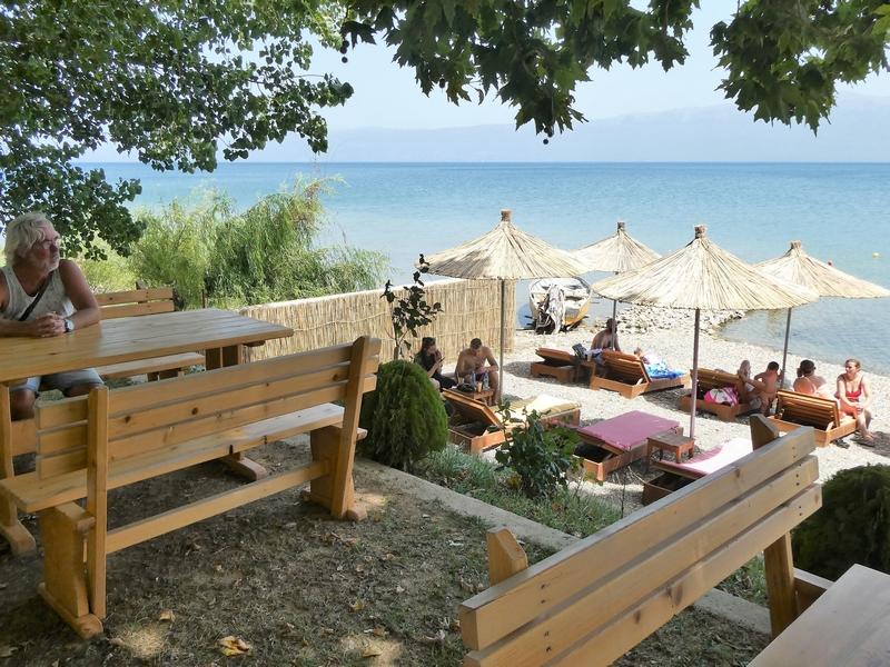 Picknicktafels en strand met ligstoelen bij strandtent Sugar Shore.
