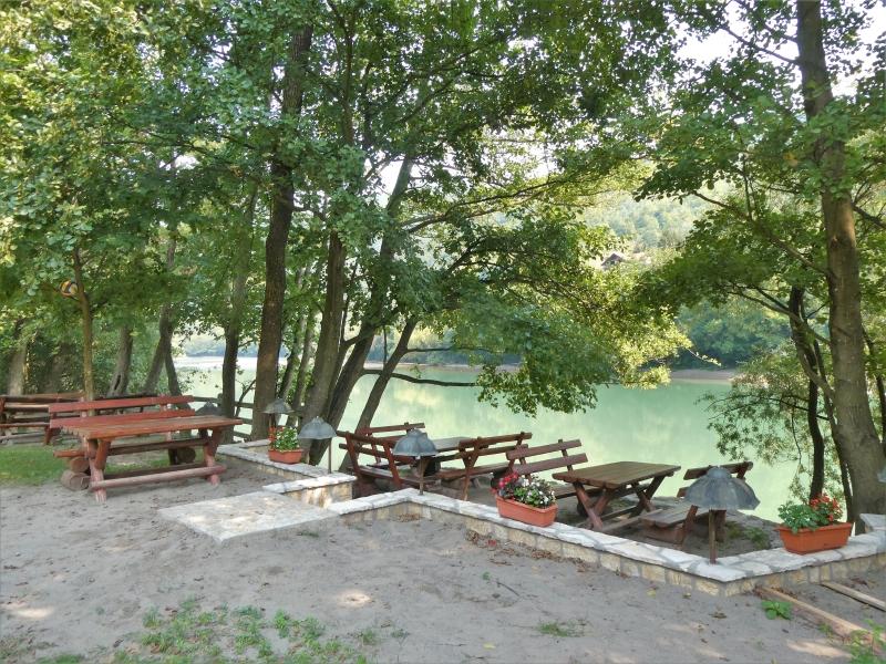 Terras van picknicktafels en -banken aan de rivier.