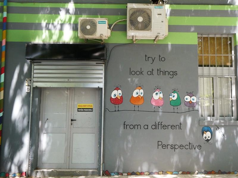 Streetart: cartooneske vogeltjes zittend op een draad. En 1 op de kop hangend. Tekst: try to look at things from a different Perspective